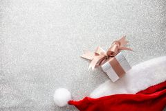 A Santa Claus hat and a small gift box on silver glitter backgro stock photography