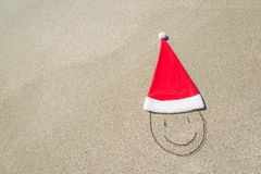Santa Claus hat and smiley face on seashore against waves Royalty Free Stock Photos
