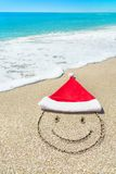 Santa Claus hat and smiley face on seashore against waves Stock Images