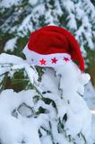 Santa Claus Hat on snowy fir Stock Photos