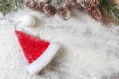 Santa Claus hat. With snowy pine cones on a snow background Royalty Free Stock Image