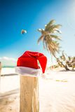Santa Claus hat on white sandy beach in sunny day Stock Photo