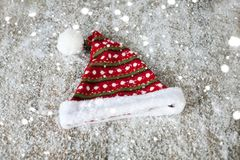 The Santa Claus hat on a wooden background in the snow Stock Photos