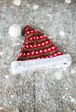 The Santa Claus hat on a wooden background in the snow Stock Photography