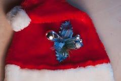 Santa Claus hatt och en kvist av järnek på tabellen, Arkivfoton