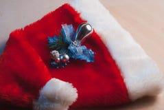 Santa Claus hatt och en kvist av järnek på tabellen, Arkivfoto