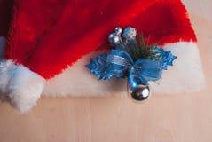 Santa Claus hatt och en kvist av järnek på tabellen, Arkivbilder