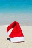 Santa Claus hatt på strandbakgrund Royaltyfri Bild