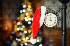 Santa Claus hatt som hänger på klockan på bakgrunden av bokeh arkivfoto