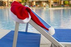 Santa Claus hatt som hänger på sunbed nära pölen Royaltyfri Fotografi