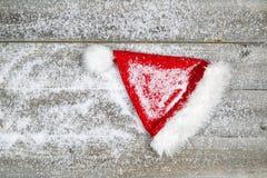 Santa Claus hatt som täckas med snö på lantligt trä Royaltyfri Bild