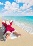 Santa Claus have a rest in chaise longue on sea beach royalty free stock images