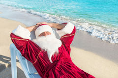 Santa Claus have a rest in lounge on sea beach Stock Photos