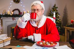 Santa Claus having coffee while holding a letter. At home Royalty Free Stock Photos