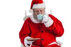 Santa claus having a cup of coffee Stock Photos