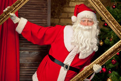 Santa Claus having fun with golden frame near  Christmas tree Royalty Free Stock Images