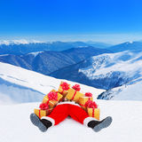Santa Claus heap with Christmas gifts against snow winter mounta Royalty Free Stock Image