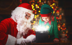 Santa Claus and helper child elf with bright magical gift in Chr Stock Photo