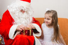 Santa Claus helps to untie ribbon gift, little girl happily looking at him Stock Photo