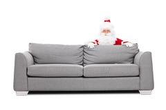 Santa Claus-het verbergen achter een bank Stock Foto's