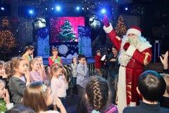 Santa Claus-het vertellen verhalen aan een groep jonge geitjes De Kerstman draagt giften Santa Claus op stadium Stock Foto