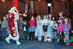 Santa Claus-het vertellen verhalen aan een groep jonge geitjes De Kerstman draagt giften Santa Claus op stadium Stock Afbeelding