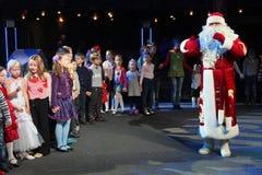 Santa Claus-het vertellen verhalen aan een groep jonge geitjes De Kerstman draagt giften Santa Claus op stadium Royalty-vrije Stock Foto