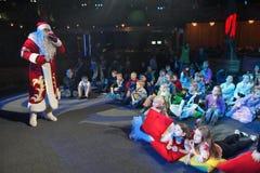 Santa Claus-het vertellen verhalen aan een groep jonge geitjes De Kerstman draagt giften Santa Claus op stadium Stock Afbeeldingen