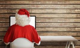 Santa Claus-het werk aangaande computer bij zijn huis Houten muur en lijst met vrije ruimte voor tekst Royalty-vrije Stock Fotografie