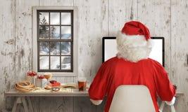 Santa Claus-het werk aangaande computer in zijn ruimte Witte houten muur met venster op achtergrond Royalty-vrije Stock Foto's