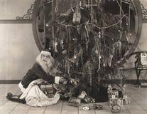 Santa Claus-het zetten stelt onder Kerstbomen voor Royalty-vrije Stock Foto's