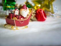 Santa Claus heureuse avec la boîte de cadeaux sur le traîneau de neige le fond est décor de Noël Décor de Santa Claus et de Noël  Photos libres de droits