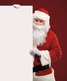 Santa Claus heureuse regardant par derrière le signe vide Image stock