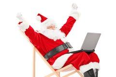 Santa Claus heureuse s'asseyant sur une chaise avec l'ordinateur portable et faisant des gestes h Images stock
