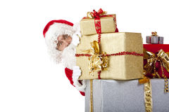 Santa Claus hiding behind christmas gift boxes. Santa  Claus is hiding behind a stack of Christmas gift boxes and looks into camera. Isolated on white Stock Photography