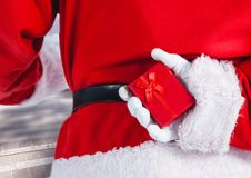 Santa claus hiding christmas gift behind his back Stock Image