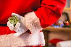 Santa claus hiding a gift box behind his back. Rear view of santa claus hiding a gift box behind his back Stock Images