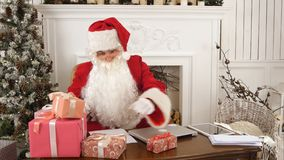 Santa Claus in his Christmas workshop signing presents for children. Professional shot on Lumix GH4 in 4K resolution. You can use it e.g. in your commercial Royalty Free Stock Photos