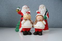 Santa Claus and his dwarf assistants. Picture of two Santa with their dwarf who carry gifts royalty free stock photography