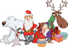 Santa Claus with his friends and Christmas gifts.  Royalty Free Stock Images