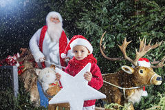 Santa Claus with his little helper and his reindeer Royalty Free Stock Photo
