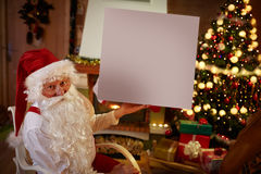 Santa Claus in his living room holding empty white banner. Christmas advert copy space stock image