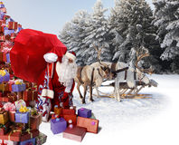 Santa Claus and his reindeer with gifts Stock Images