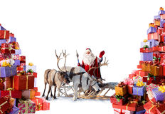 Santa Claus with his reindeer and gifts. Santa Claus with reindeer stand beside the huge amount of gifts, which he is going to give for you during Christmas Stock Photography