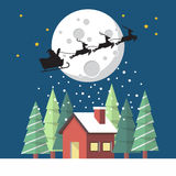 Santa Claus and his reindeer sleigh in silhouette against moon w Stock Photos