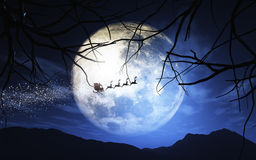Santa Claus and his sleigh flying in a moonlit sky Stock Images