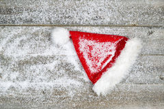 Santa Claus-hoed die met sneeuw op rustiek hout wordt behandeld Royalty-vrije Stock Afbeelding