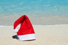 Santa Claus-hoed op het strand Stock Afbeeldingen