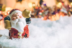 Santa claus hold the bell and star stand among pile of snow at silent night,  light up the hopefulness and happiness in Merry chri Stock Images
