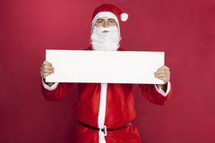 Santa Claus is holding an advertisement in front of him,. On the red background stock photos